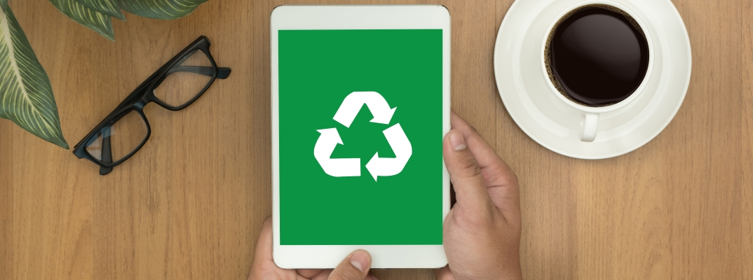 Hands holding an iPad with a recycle symbol on the screen